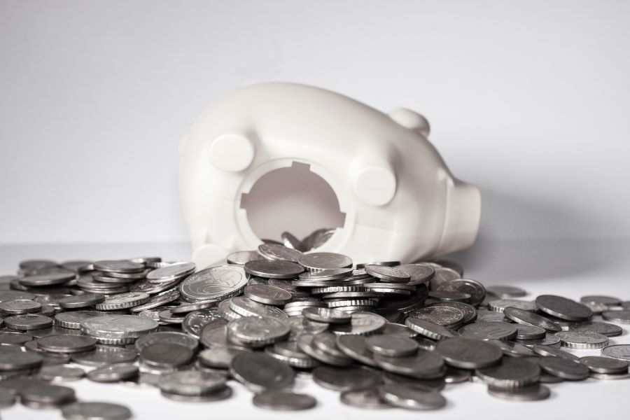 Tipped over piggy bank with money