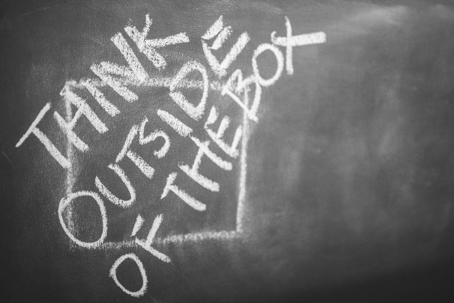 """Think Outside of the box"" written on a chalkboard"