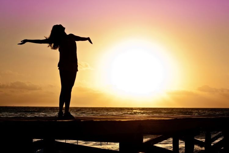 Woman at sunset - feeling relief after paying off debt