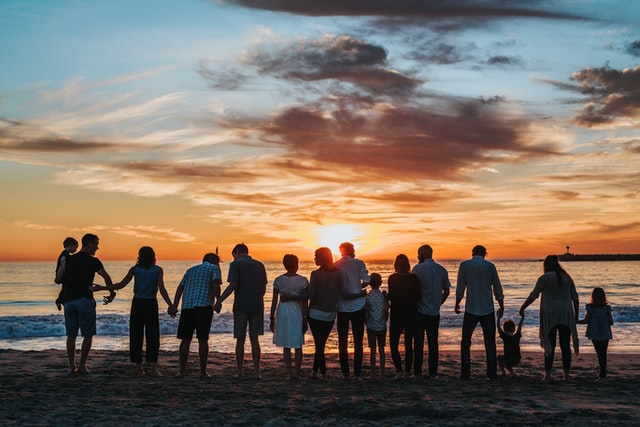 Multi-generational family holding hands on the beach at sunset