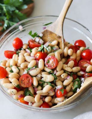 A glass bowl full of Cannellini Bean Salad