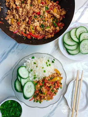 A bowl of chili garlic tofu scramble with rice and cucumbers.  The cooked dish of Chili Garlic Tofu Scramble and a bowl of cucumbers on the side.