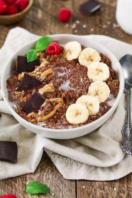 A breakfast bowl filled with quinoa, bananas, and chocolate