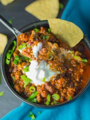 A bowl of chili topped with sour cream, green onions, and tortilla chips