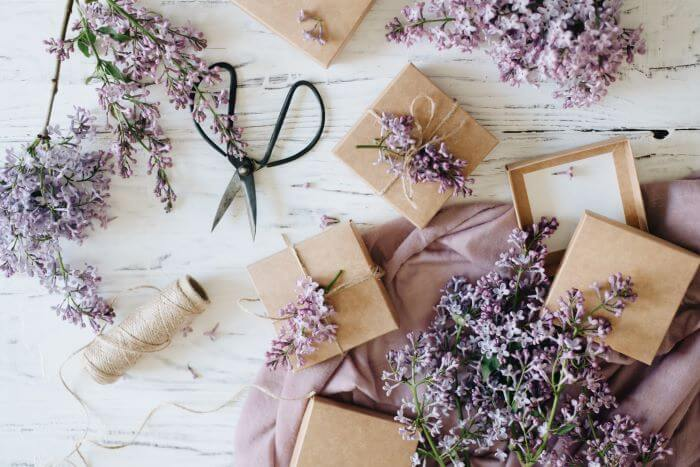 Small presents wrapped in craft paper and decorated with purple flower