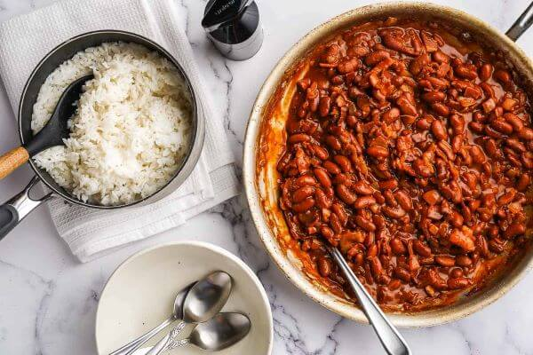 A pan with cooked red beans and a bowl of white rice on the side