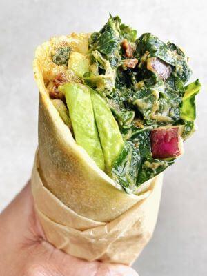 Someone holding a Raw Kale Wrap Sandwich
