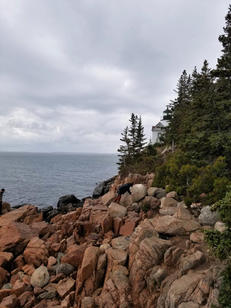 Rocky shoreline of Acadia National Park with Schoodic Head LIghthouse in the background