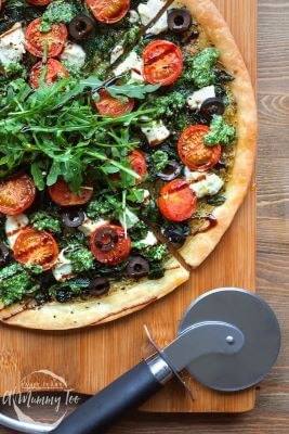 A cutting board with a Spinach and Goat's Cheese Arugula Tart on it.  Pizza cutter is placed on the side.