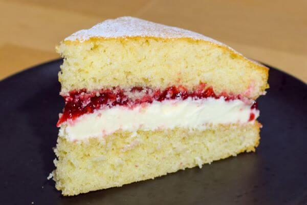 A slice of a Victoria Sponge Cake on a black plate