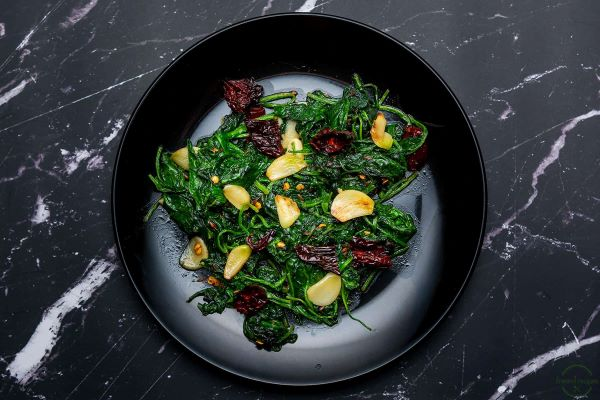 A black bowl filled with Wilted Spinach, Garlic Slices, and Chilis