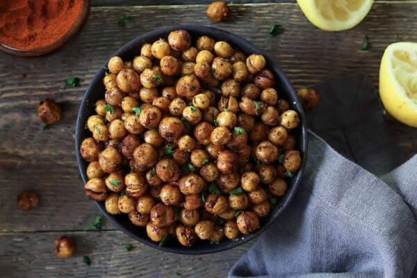 A bowl of air fried chickpeas with Lemon wedges on the side