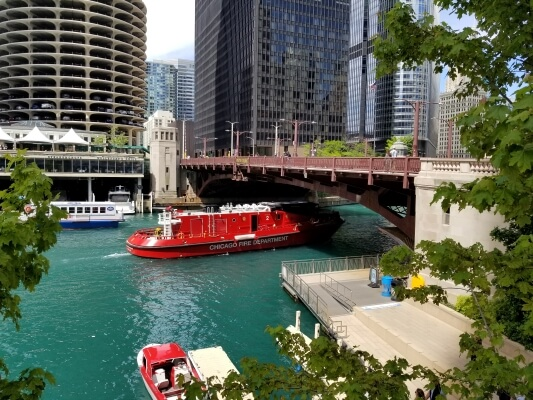 Fire boat on the Chicago River with skyscrapers in the background
