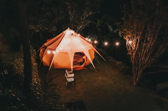 A night time picture of A lit up Yurt with String lights outside